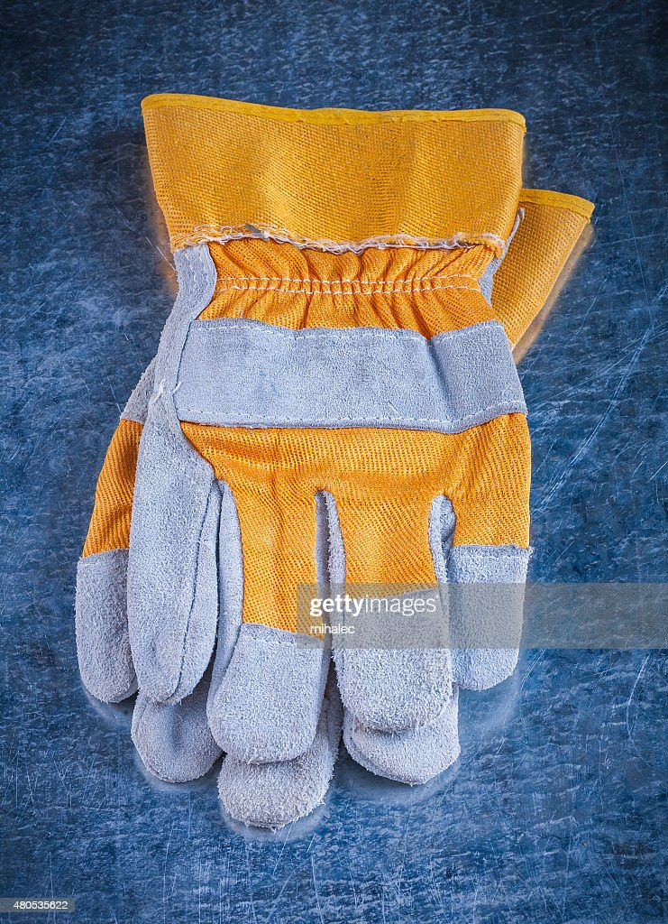 Protective working gloves on scratched vintage metallic backgrou : Stock Photo