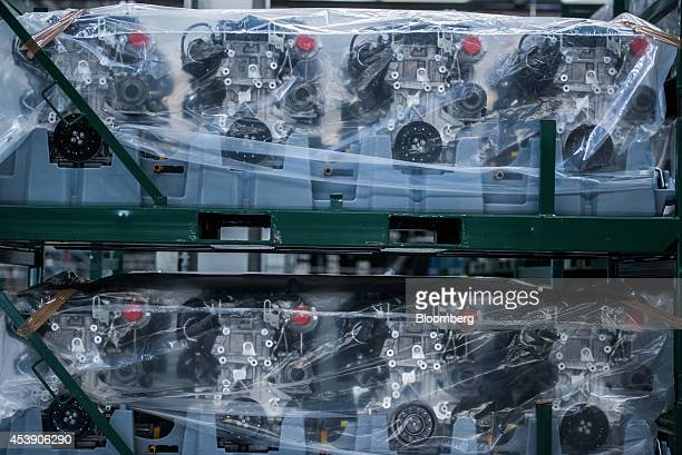 Protective wrapping covers finished automobile motors sitting in storage racks following assembly at the Adam Opel AG gasoline and diesel engine...