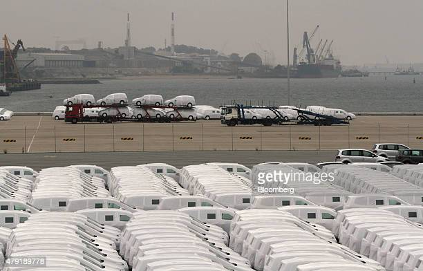 Protective wrapping covers new trucks as automobiles pass along the quayside on a vehicle transporter at the Autoeuropa rollon/rolloff terminal in...