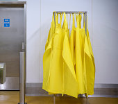 Protective yellow aprons hanging up in food factory
