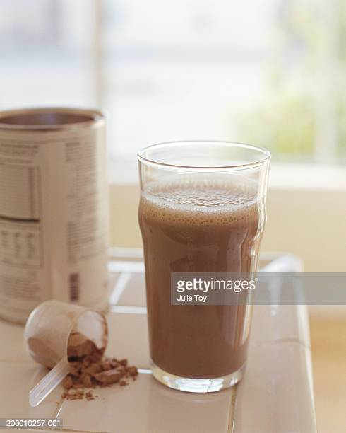Protein drink with can and measuring cup on counter