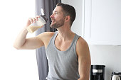 A man in a kitchen drinking a protein shake