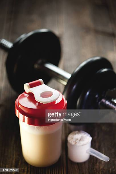 Protein shake with a dumbbell and measuring scoop.
