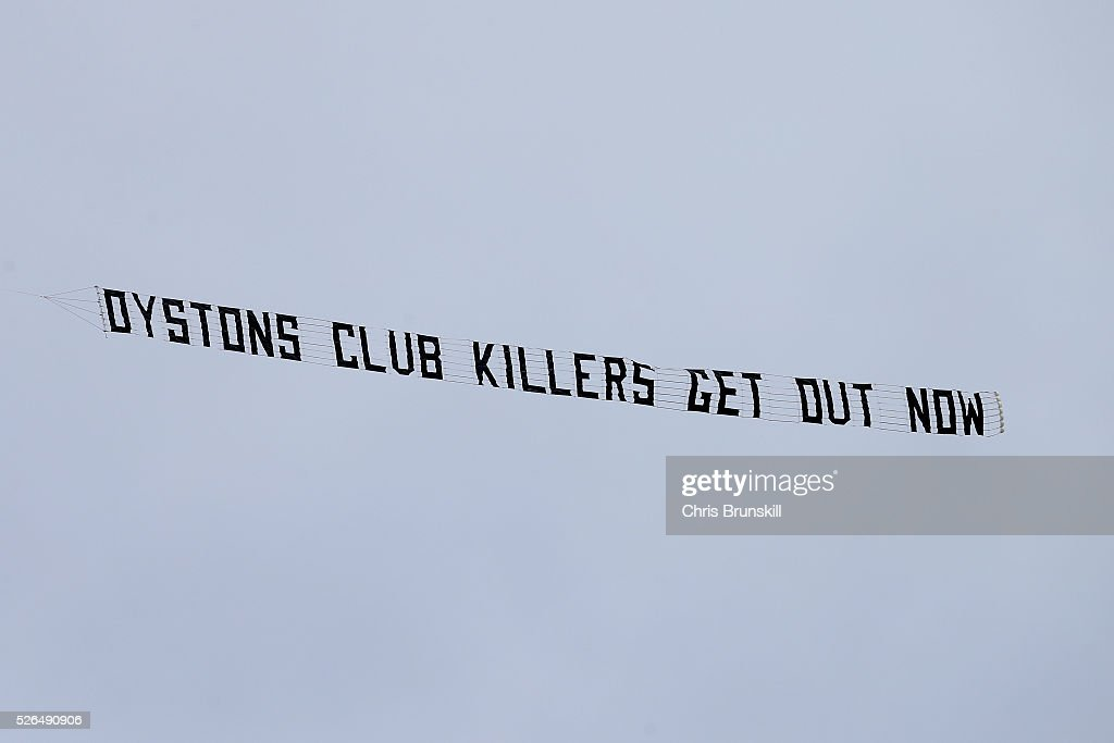 A protest banner reading 'Oyston club killers get out now' is flown over the stadium during the Sky Bet League One match between Blackpool and Wigan Athletic at Bloomfield Road on April 30, 2016 in Blackpool, England.