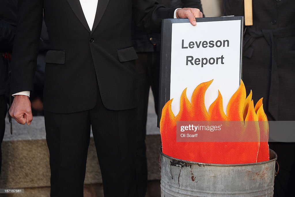A protest group campaigning against the political dominance of Rupert Murdoch stage a mock burning of a copy of the Leveson Report outside the Queen...