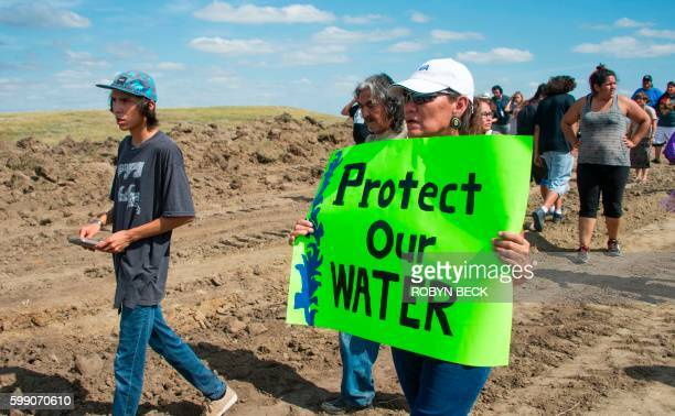 A protest holds a sign reading Protect Our Water as Native Americans and their supporters walk on land designated for the Dakota Access Pipeline...