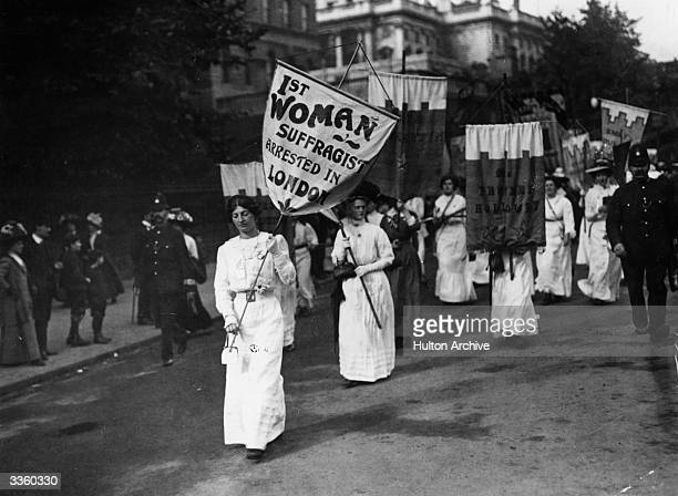 A protest march by women suffragettes in London with police in attendance The banner held by the leading women reads '1st Woman Suffragist Arrested...