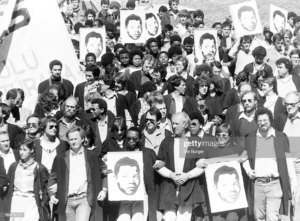 A protest march held by members of South Africa's education dapartment, demonstrating for the release of anti-apartheid activist, Nelson Mandela. They are holding posters of Nelson Mandela.