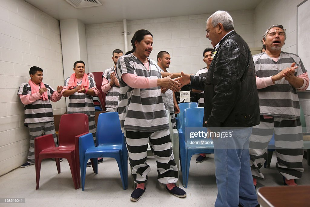 A Protestant minister greets immigrant inmates at church service at the Maricopa County Tent City jail on March 11, 2013 in Phoenix, Arizona. Striped uniforms and pink undergarments are standard issue at the facility. The tent jail, run by Maricopa County Sheriff Joe Arpaio, houses undocumented immigrants who are serving up to one year after being convicted of crime in the county. Although many of immigrants have lived in the U.S for years, often with families, most will be deported to Mexico after serving their sentences.