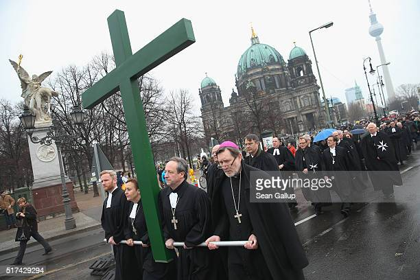 Protestant pastors carry a cross during a procession through the city center to mark Good Friday on March 25 2016 in Berlin Germany Christians across...