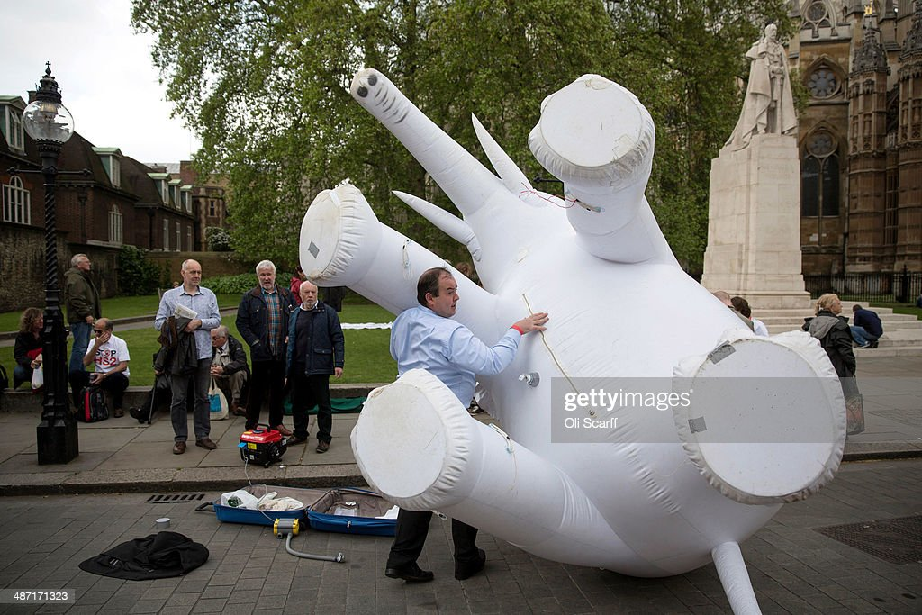 A protester against the Government's proposed high-speed rail link (HS2) moves an inflatable white elephant during a demonstration outside the Houses of Parliament on April 28, 2014 in London, England. The House of Commons will vote later today on the HS2 bill's second reading with 30 Conservative MPs threatening to vote against the Government's pro-HS2 stance.