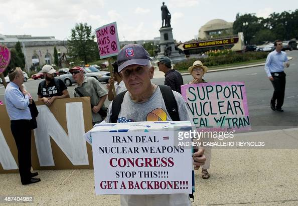A protester against the international nuclear agreement with Iran stands in front of Code Pink activists in support of the email during a Tea Party...
