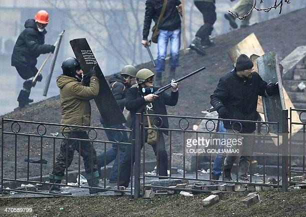 A protester aims a rifle towards riot police as protesters advance to new positions advance to new positions near the Independence square in Kiev on...