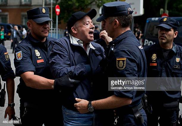 A protester argues with police as he is removed from Canovas del Castillo square during a protest calling for a Referenderum surrounding the Spnish...