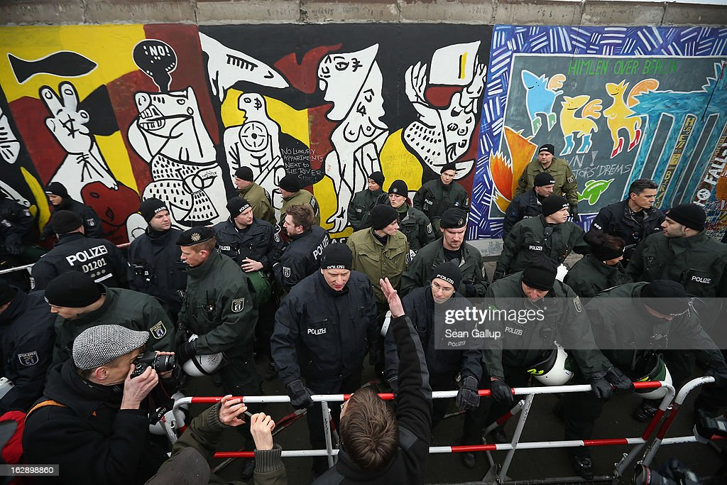 A protester argues with police at the East Side Gallery, which is the longest still-standing portion of the former Berlin Wall, following efforts by a construction company to remove a 25-meter long section of the Wall on March 1, 2013 in Berlin, Germany. A real estate developer is planning to build a 14-storey apartment building between the East Side Gallery and the Spree River, and needs to remove the Wall section in order to allow access to the construction site. Critics, including East Side Gallery mural artists and Spree River embankment development opponents, decry the move, citing the importance of the East Side Gallery's status as a protected landmark and a major tourist attraction. The East Side Gallery is approximately 1.3 kilometers long.