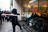 A protester attempts to smash a Starbucks window during a demonstration against fees and cuts in the education system on November 19 2014 in London...