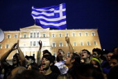 A protester brandishes a Greek flag as he demonstrates with thousands protesters against a new austerity package in front of the Greek parliament in...