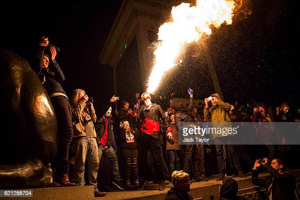 A protester breathes fire as masked protesters gather in Trafalgar Square during the Million Mask March on November 5 2016 in London England...
