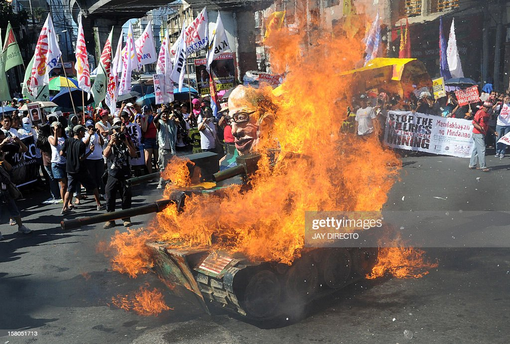 Protester burn and effigy of Philippine President Benigno Aquino on board a mock tank as they commemorate International Human Rights Day near the Presidential Palace in Manila on December 10, 2012. The protesters are calling out the Aquino administration as the number one human rights violator. They accusing the government because of the alleged militarization of the countryside. Thirty five anti-mining and environment advocates, most of whom are indigenous people, have been allegedly killed by the military because of their strong opposition to the entry of multinational companies they accuse of plundering their land. AFP PHOTO / JAY DIRECTO