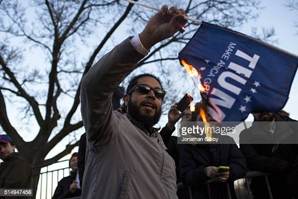 A protester burns a flag outside of the University of Illinois at Chicago Pavilion where Republican presidential candidate Donald Trump is due to...
