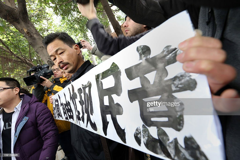A protester calling for greater media freedom outside the headquarters of Nanfang Media Group in Guangzhou holds up a banner saying 'freedom of press reflects the public's opinion' in Chinese on January 9, 2013. A Chinese weekly newspaper at the centre of rare public protests about government censorship will publish as usual on January 10, a senior reporter said, following reports of a deal to end the row. The row at the popular liberal paper, which had an article urging greater rights protection replaced with one praising the ruling communist party, has seen demonstrators mass outside its headquarters in the southern city of Guangzhou. AFP PHOTO