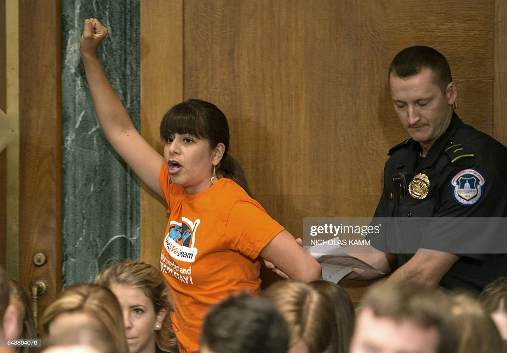 A protester calling for the end of deportations of undocumented immigrants is removed by police as Homeland Security Secretary Jeh Johnson testifies at a Senate Judiciary Committee hearing on 'Oversight of the Department of Homeland Security' on Capitol Hill in Washington, DC, on June 30, 2016. / AFP / NICHOLAS