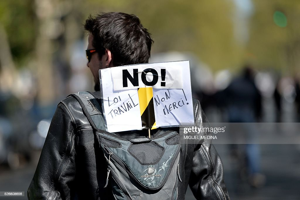 A protester carries a backpack bearing a placard reading 'No to the labour law, No thank you!' during a traditional May Day demonstration on May 1, 2016, in Paris.