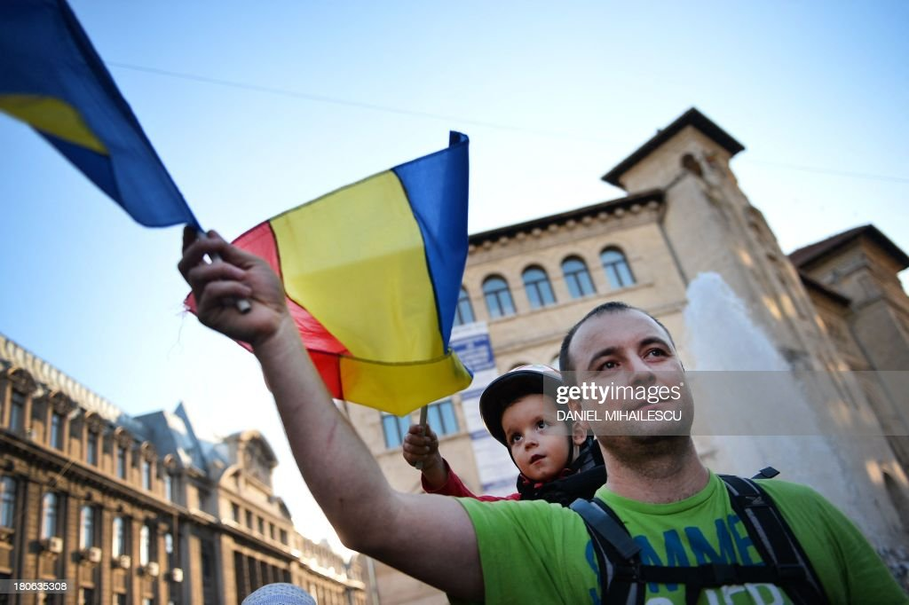 A protester carries a child and waves the Romanian flag as he takes part in the fifteen day of demonstrations, September 15, 2013 in Bucharest, Romania against the Rosia Montana Gold Corporation (RMGC).Thousands of young Romanians have taken to the streets for almost two weeks in protest against plans, supported by the government, for Europe's biggest open-cast gold mine, a civic movement unprecedented since the 1990s.