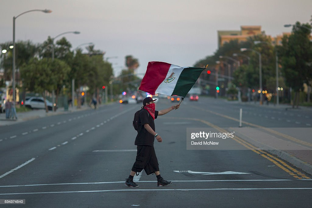 A protester carries a Mexican flag after a campaign rally by presumptive GOP presidential candidate Donald Trump at the Anaheim Convention Center earlier in the day on May 25, 2016 in Anaheim, California. Previous visits by the candidate to Orange County have sparked protests that resulted in some arrests. The presidential candidates are campaigning in Southern California for the June 7 California primary.