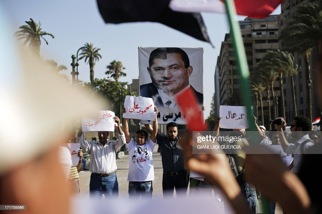 A protester carries a poster depicting the current Egyptian President Mohamed Morsi and ousted president Hosni Mubarak during a demonstration against...
