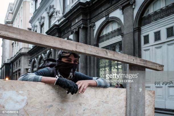 A protester carries a wooden shield against military police during the nationwide strike called by unions opposing austerity reforms in Rio de...
