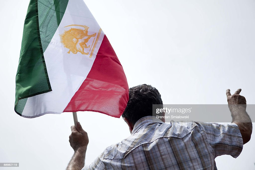 A protester carries the Iranian flag during a rally July 11, 2009 in Washington, DC. Activists gathered to rally for the current uprising in Iran over the recent elections.