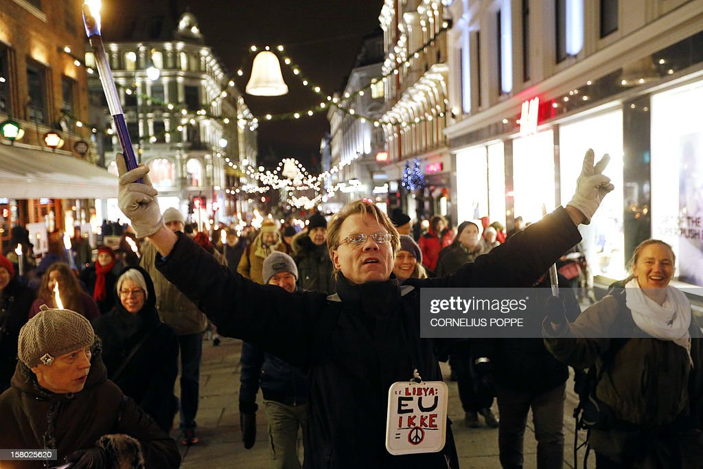 A protester carrying a lit torch raises his arms during a protest in central Oslo on December 9, 2012, against the Norwegian Nobel Committee's award of the 2012 Peace Prize to the EU. AFP PHOTO /CORNELIUS POPPE/SCANPIX NORWAY /NORWAY OUT