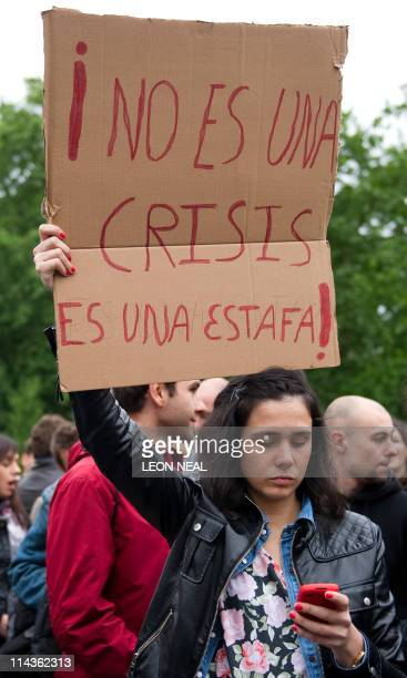 A protester checks her mobile phone as she holds a sign that reads Its not a crisis it's a scam' during a demonstration over the current economic...