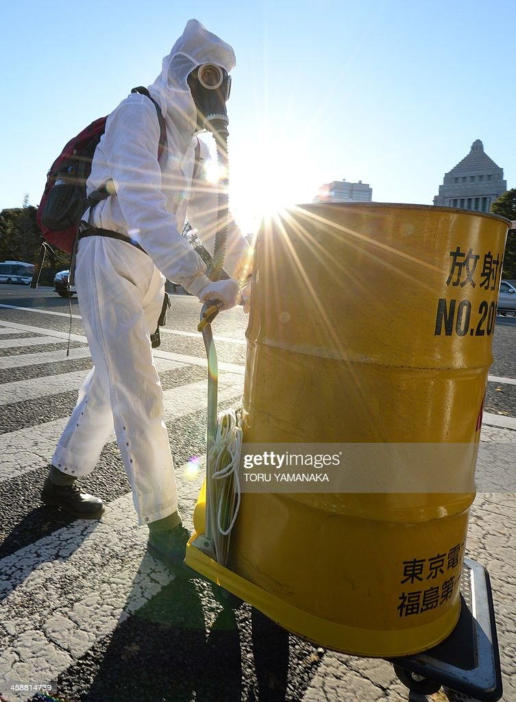 A protester clad in protective suits carries a barrel of mock nuclear waste during a rally denouncing the Japanese government direction to resume nuclear power plants in front of the national Diet in Tokyo on December 22, 2013. Several thousands of people gathered at the rally againt nuclear power plants around the Diet. AFP PHOTO/Toru YAMANAKA