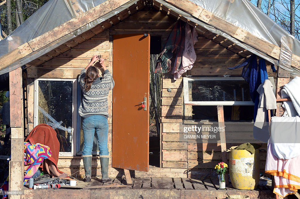 A protester cleans a wooden house after re-occupying a protected swampland on November 25, 2012 in Notre-Dame-des-Landes, near Nantes in western France, one day after squatters' eviction and clashes with anti-riot policemen. The airport, which is scheduled to replace the current airport at Nantes in 2017, is a pet project of Socialist Prime Minister Jean-Marc Ayrault, who was the city's mayor from 1989 until this year.