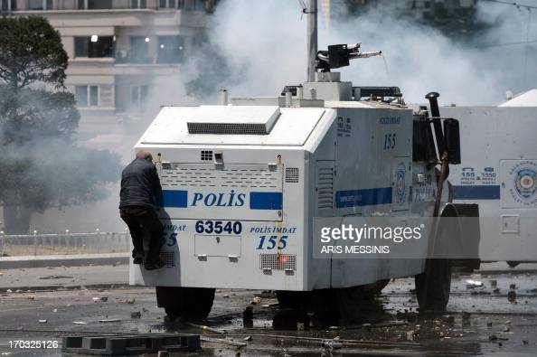 A protester climbs up onto a riot police van equipped with a water canon during clashes at Taksim square in Istanbul on June 11 2013 Riot police...