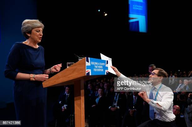 Protester comedian Simon Brodkin delivers a piece of paper written as a mock P45 to Britain's Prime Minister Theresa May as delivers her speech on...