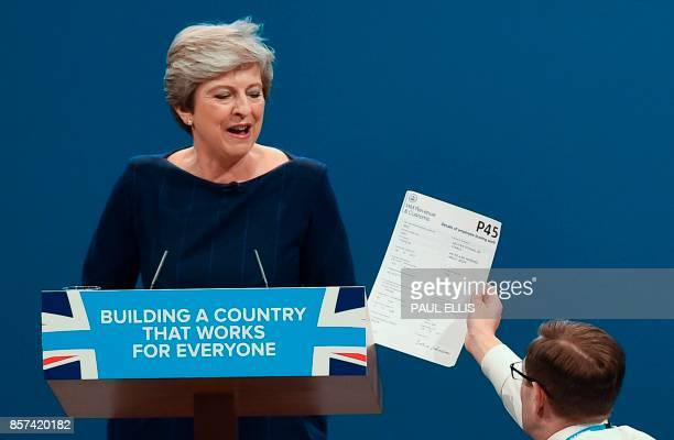 TOPSHOT Protester comedian Simon Brodkin gives a piece of paper written as a mock P45 to Britain's Prime Minister Theresa May as she was delivering...