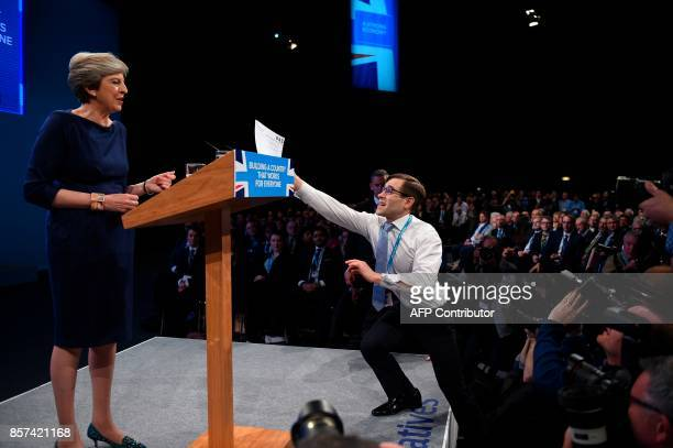 Protester comedian Simon Brodkin gives a piece of paper written as a mock P45 to Britain's Prime Minister Theresa May as she was delivering her...
