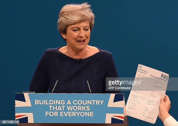 Protester comedian Simon Brodkin hands a piece of paper written as a mock P45 to Britain's Prime Minister Theresa May as she was delivering her...