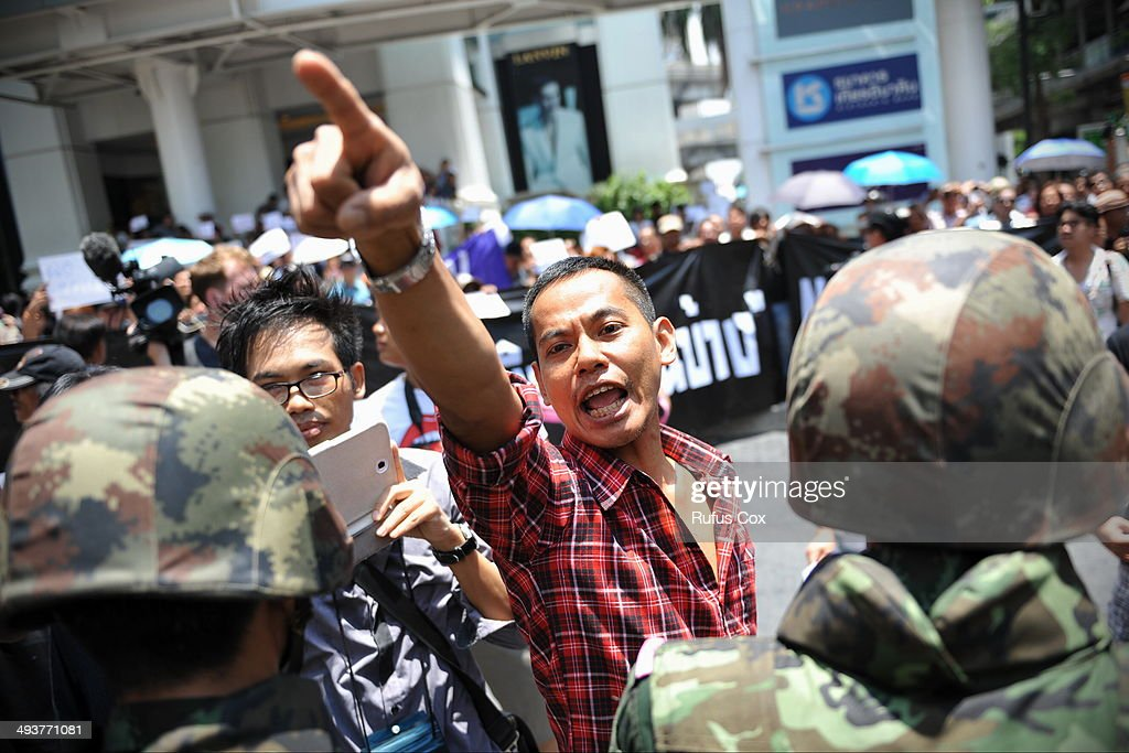 A protester confronts soldiers in riot gear during a city centre anti-coup rallly on May 25, 2014 in Bangkok, Thailand. Several hundred protesters gathered in central Bangkok, defing a martial law decree that prohibits public assembly. The Thai armed forces seized power in the May 22 coup after months of street protests and political unrest.