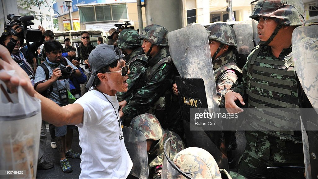 A protester confronts Thai soldiers in riot gear during a city centre anti-coup rallly on May 25, 2014 in Bangkok, Thailand. Several hundred protesters gathered in central Bangkok, defing a martial law decree that prohibits public assembly. The Thai armed forces seized power in the May 22 coup after months of street protests and political unrest.