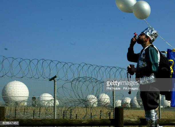 A protester covered in silver foil in an attempt to disrupt radar equipment blows a whistle during a demonstration against war with Iraq outside RAF...