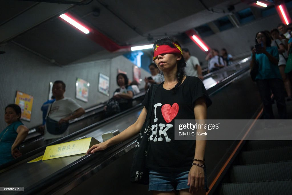 A protester covers her eyes with a China flag to imply Goddess of Justice during the rally supporting young activists Joshua Wong, Nathan Law and Alex Chow in central on August 20, 2017 in Hong Kong, Hong Kong. Pro-democracy activists Joshua Wong, Nathan Law and Alex Chow were jailed last week after being convicted of unlawful assembly.