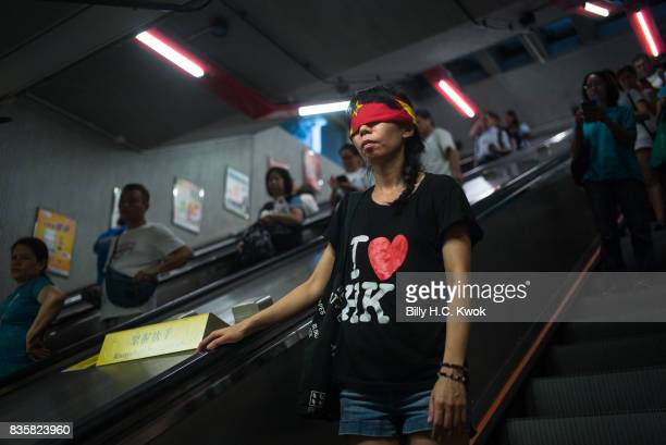 A protester covers her eyes with a China flag to imply Goddess of Justice during the rally supporting young activists Joshua Wong Nathan Law and Alex...