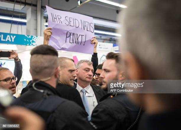 A protester demonstrating against the presence of farright publishing houses and the visit of a regional leader of the AfD holds up a poster reading...