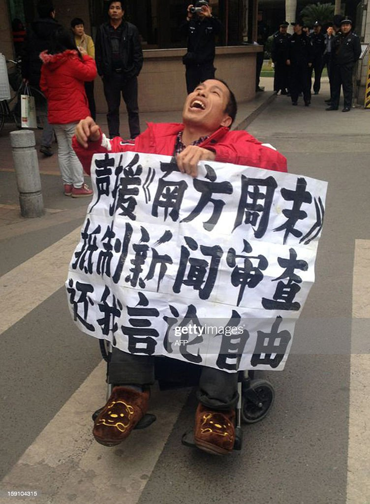 A protester displays a banner to support journalists from the Southern Weekend newspaper near the company's offices in Guangzhou, south China's Guangdong province on January 8, 2013. Chinese bloggers and celebrities along with foreign media campaigners threw their support behind journalists at a newspaper enmeshed in a censorship row on January 8, after a rare protest for press freedom.CHINA