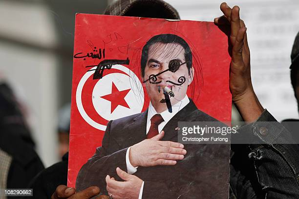 A protester displays a defaced portrait of ousted president Zine alAbidine Ben Ali outside the Tunisian prime ministers office on January 24 2011 in...