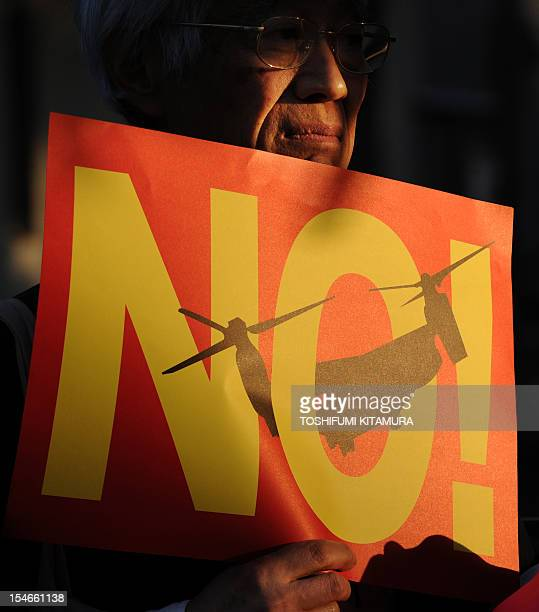 A protester displays a 'No' poster featuring US MV22 Osprey aircraft during their protest rally against US military bases in Okinawa in front of...